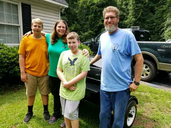 David C., with family picking up their Carolina Pig Cooker.